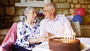 couple holding hands at birthday party