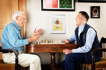 male carer and client playing chess