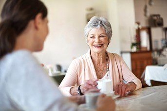 Lady and carer enjoying a cup of tea and smiling